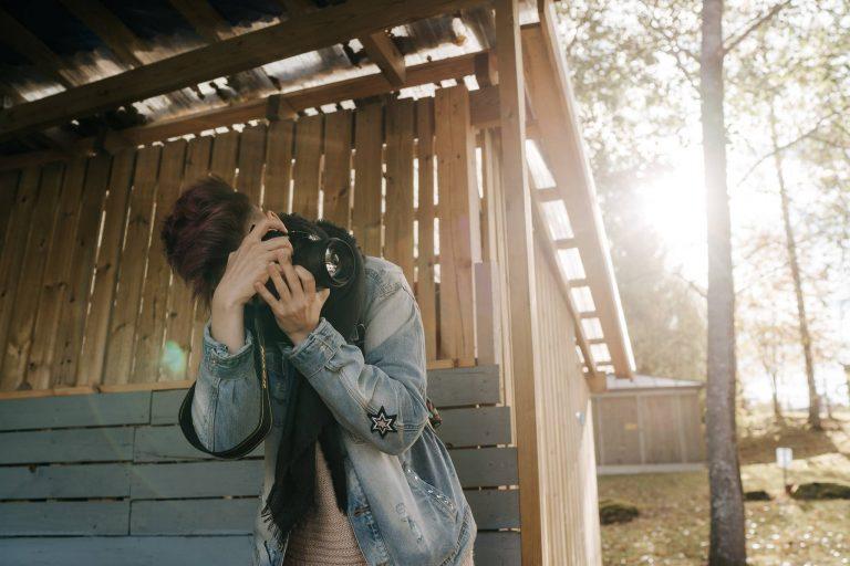 Lyhythiuksinen nainen on kumartunut kuvaamaan järjestelmäkameralla. Päällään hänellä on farkkutakki, sen alla villapaita ja kaulassa kaulahuivi