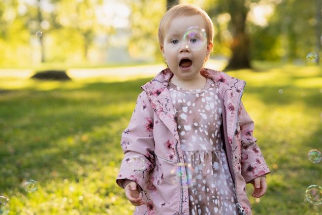 Lapsi seisoo aurinkoisessa maisemassa saippuakupla silmän edessä