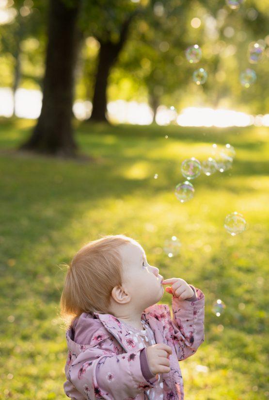Lapsi näyttää pohtivalta katsoessaan ylös saippuakuplien leijailua